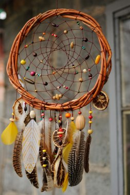 Handmade dream catcher at wall in background