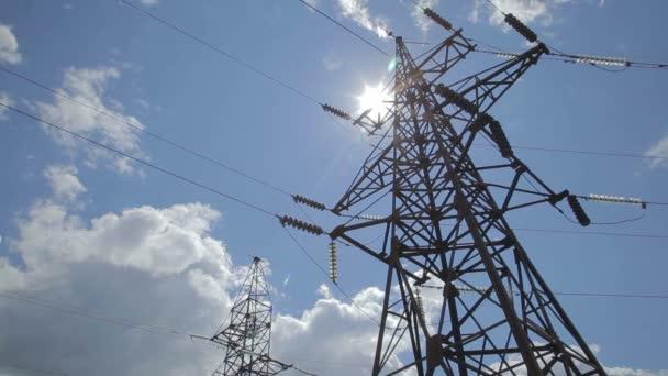 stožárů vysokého napětí moc proti modré oblohy a sluneční paprsky