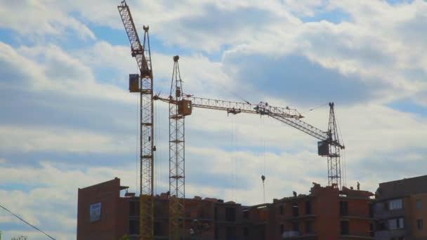 Staveniště na území bývalého Sovětského svazu. Práce jeřáby proti obloze.