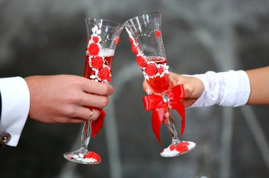 Unusual and original Wedding glasses decorated with roses. Bride and groom holding champagne glasses. Champagne Toast . Wedding glasses in their hands in selective focus. Backyard party background.