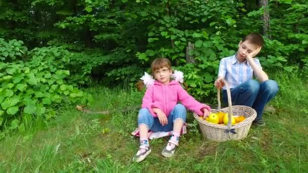 Děti už cpal a nechce jíst ovoce. Dívka, šňupání Meruňka. Chlapec hodí oranžová