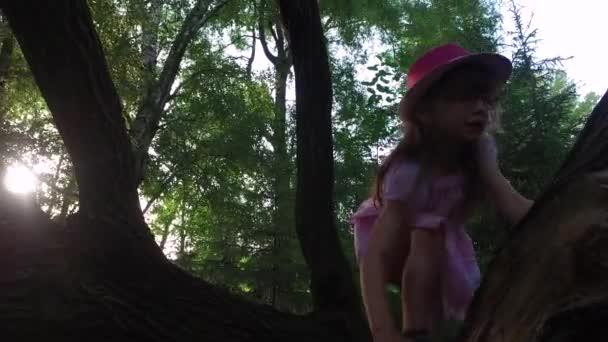 Dívčí dítě se pokouší vylézt na strom. Ale nemůže. Je stále malá.