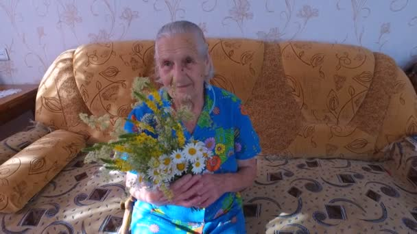 Old woman sitting on a couch in his apartment. She holds flowers in hands. The quiet old age.