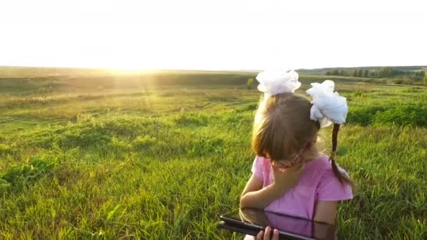 Little girl with enthusiasm plays on the tablet PC. Girl child with glasses stands on a green meadow.