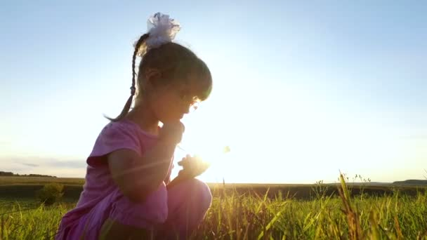 Little girl with enthusiasm plays on the smartphone. Girl child in glasses sits on a green meadow.