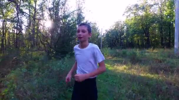 Slim teenager boy is running on paths and trails in the forest. Boy is trained good running. Sports in nature.