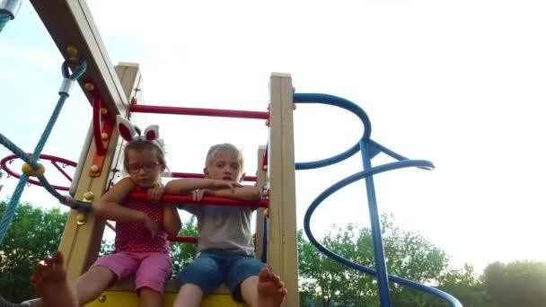 Dívka s ušima a brýle a chlapce s bílými vlasy, baví na dětské věž