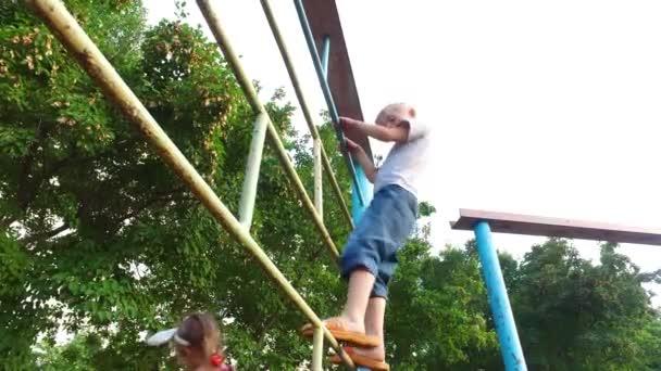 Klettergerüst English : Junge kind mit weißen haaren steigt auf dem klettergerüst