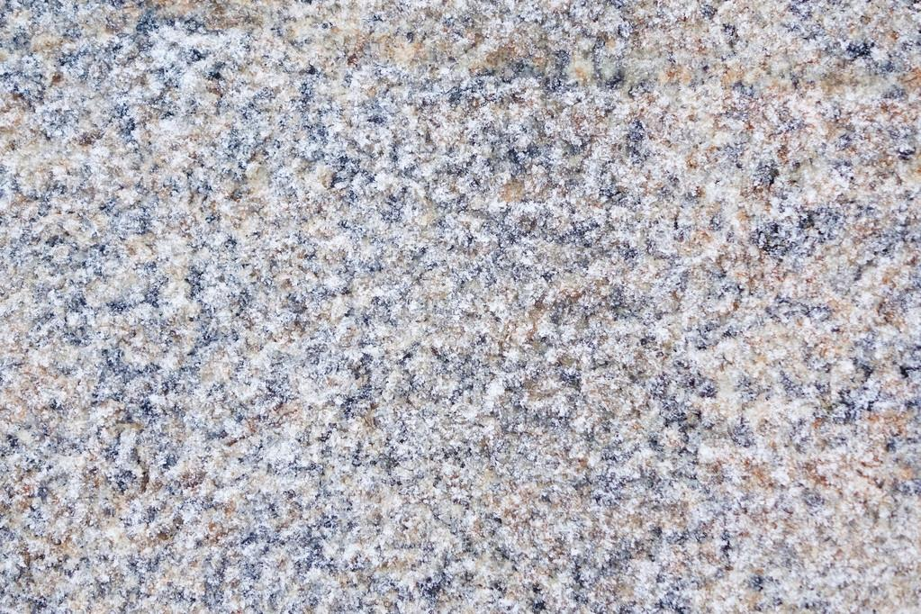 Winter background stone granite slab covered with frost