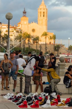 Sitges, Spain - 21 August 2016: Africans sell counterfeit goods for tourists on promenade of Sitges.