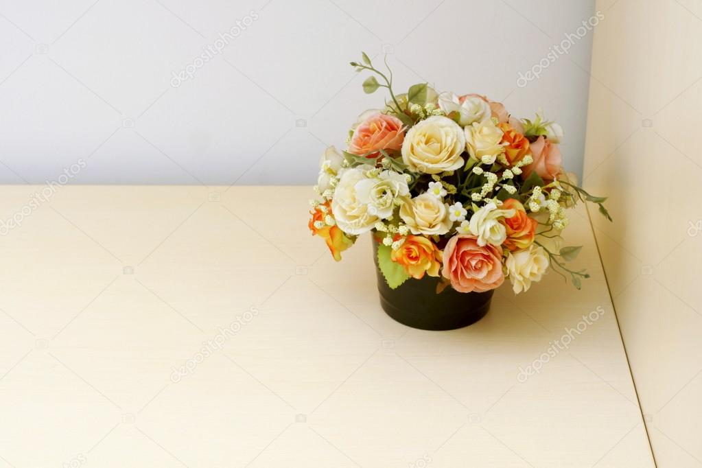 Artificial flowers on wood table