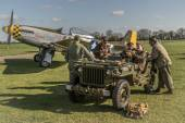 Ground crew sit in a WW2 jeep with a P-51 Mustang in the backgro