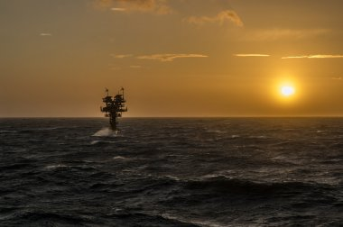 Caravel unmanned gas platform in rough seas silhouetted against