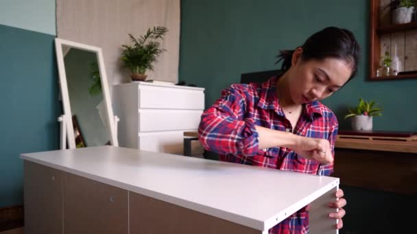 Ethnic Asian female sitting on floor and screwing wooden board while assembling new furniture at home