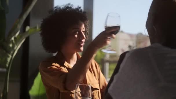 Seitenansicht einer fröhlichen Afroamerikanerin mit lockigem Haar, die im Café sitzt und Rotwein trinkt, während sie sich entspannt und mit einem unkenntlichen Freund mit kurzen Haaren spricht
