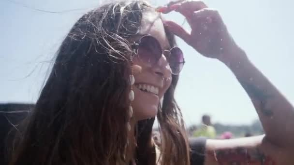 Closeup slow motion view of delighted young female traveler with piercing and stylish sunglasses enjoying freshness of waterfall splashes while visiting Montmorency Falls in Canada in sunny summer day