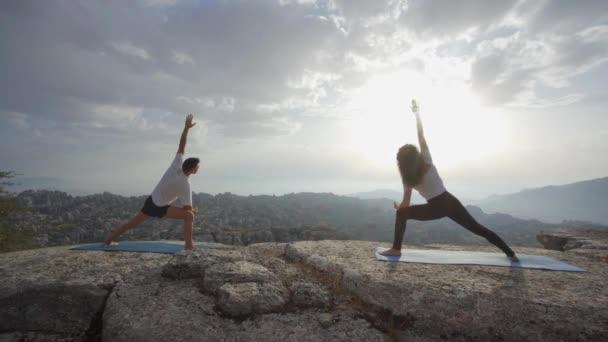 Ganzkörper-Seitenansicht von Mann und Frau in Aktivkleidung, die mit erhobenen Armen in Berg-Pose stehen, während sie gemeinsam Yoga vor bergiger Landschaft praktizieren