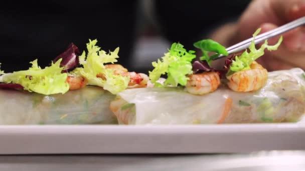 Nerozpoznatelný kuchař zdobení kachní cannelloni s čerstvou zelení sloužil na talíři v kavárně