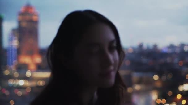 Ruhige Frau steht am Fenster in der Wohnung und blickt fröhlich in die Kamera auf verschwommenem Hintergrund der Stadtlandschaft am Abend