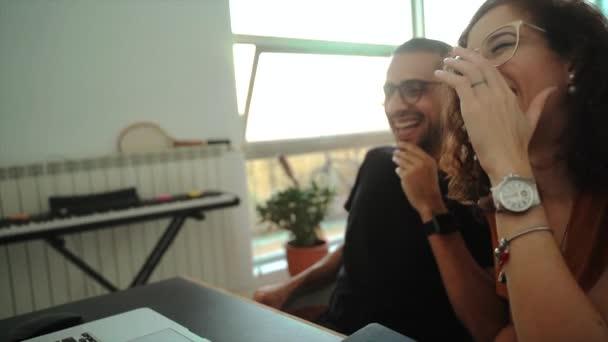 Fröhliches junges Paar in lässiger Kleidung und Brille hält Händchen, während es zusammen auf dem Sofa sitzt und Videotelefonie am Laptop hat