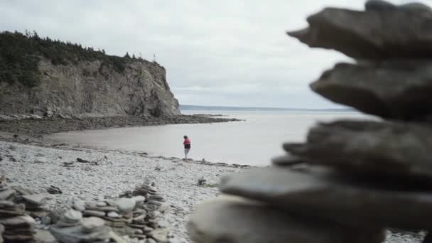 Blick zurück auf anonyme Touristinnen, die im Urlaub in Peggys Cove, Kanada, am felsigen Meer entlang wandern