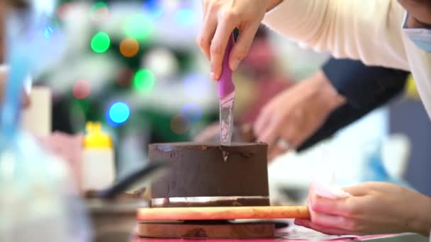 Crop unrecognizable woman with knife aligning chocolate cake while cooking in professional bakery
