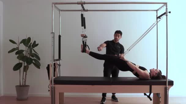 Seitenansicht einer konzentrierten Sportlerin, die Übungen auf dem Pilates-Reformer macht, während sie im Fitnessstudio auf die Ratschläge ihres persönlichen Trainers hört