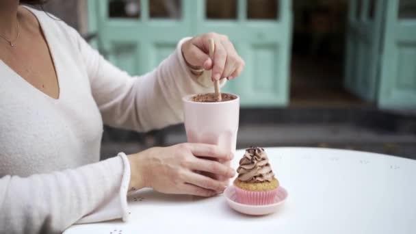 Seitenansicht von beschnitten unkenntlich erwachsene Frau in lässiger Kleidung sitzt am Tisch auf der Terrasse der gemütlichen Cafeteria und genießt Frappe Kaffee und Kuchen