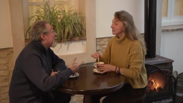 Side view boldog idős férfi és nő csevegő barátságos és élvezi a forró kávét, miközben ül az asztalnál, közel a kandalló hangulatos szobában