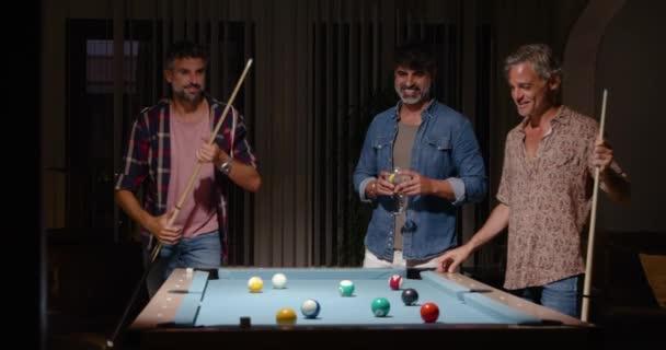 Happy starší přátelé v ležérní oblečení hraní bazénu a pití koktejlů při odpočinku v útulné místnosti ve světle lamp