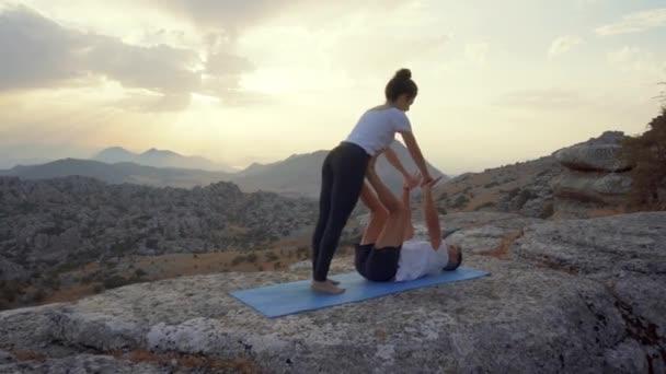 Ganzkörper-Seitenansicht fokussierter Männer und Frauen, die Akro-Yoga praktizieren und Front Plank Asana auf dem Gipfel des felsigen Berges machen
