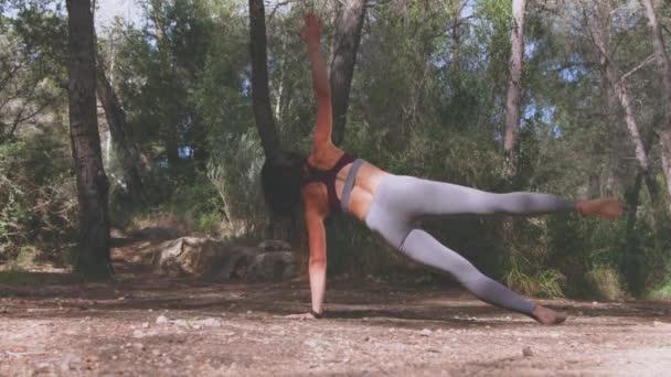 Rückenansicht einer anonymen jungen Frau in Sportbekleidung, die Vasisthasana barfuß praktiziert, um das Gleichgewicht zu entwickeln und die Muskeln von Bauch und Armen im Kiefernwald zu stärken