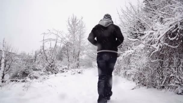 Anonymous man walking on snowy path