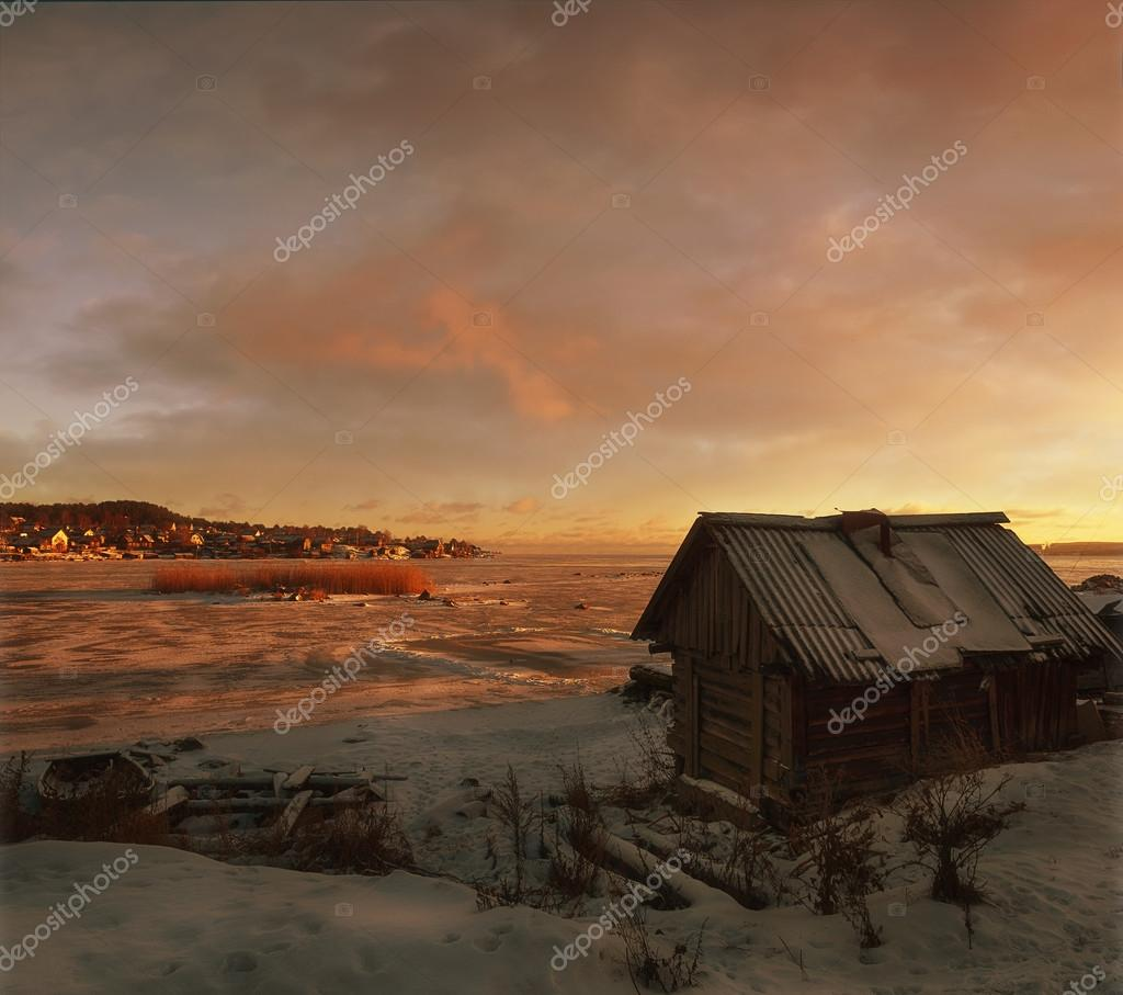 The russian bath. The lake winter, a sunset. In the background a village.