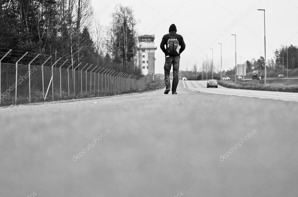 View of young man walking on road near airport