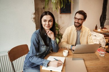freelancer in glasses using laptop and looking at woman in cafe