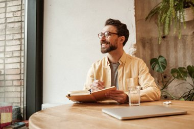 cheerful bearded freelancer in eyeglasses holding notebook and looking away