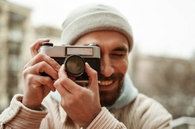 Bearded photographer in beanie hat smiling while taking photo on retro camera stock vector