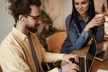bearded freelancer in wireless earphones using laptop near woman with cup on blurred background