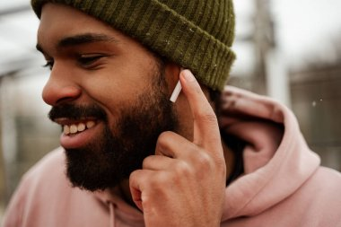 smiling, bearded african american man adjusting earphone while listening music outdoors