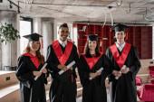 boldog fajok közötti diákok ballagási ruhák és sapkák birtokában diploma, senior 2021