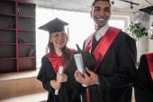vidám fajok közötti diákok ballagási ruhák és sapkák birtokában diploma, senior 2021