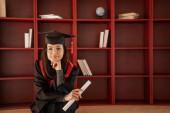 barna tanuló szemüvegben, ballagási sapka és köpenytartó diploma