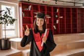 boldog tanuló szemüvegben, ballagási sapka és köntös tartó diploma, miközben mutatja hüvelykujját felfelé