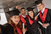 izgatott fajok közötti diákok ballagási ruhák és sapkák birtokában diploma, senior 2021