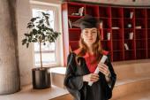 vörös hajú diák diplomás sapkában és köntösben
