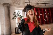 izgatott vörös hajú diák ballagási sapkában és köpenytartó diplomával