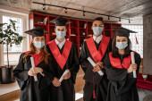 fajok közötti hallgatók orvosi maszkban, ballagási köpenyben és sapkában, végzős 2021