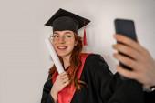 jókedvű diák ballagási sapkában és köntösben selfie, senior 2021