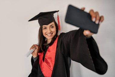 Happy student in graduation cap and gown taking selfie, senior 2021 stock vector
